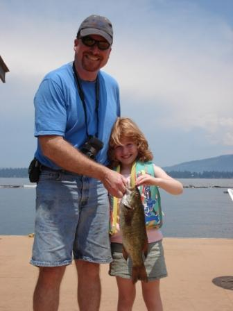 Father and daughter holding up a small mouth bass